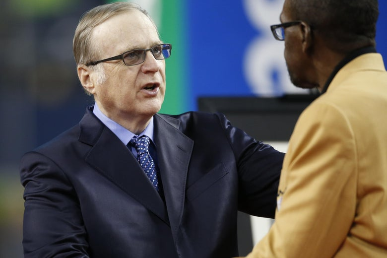 Paul Allen greets an NFL Hall of Fame member during halftime of a Seahawks game.