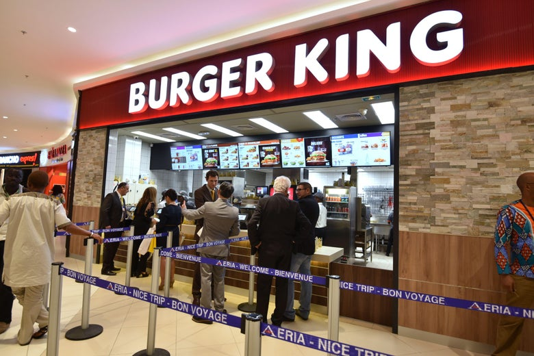 People wait in line at an airport Burger King.