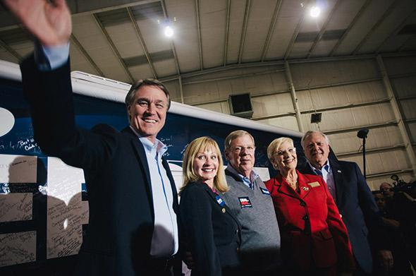David Perdue, Bonnie Perdue, Senator Johnny Isakson, Sandra Dunagan Deal, and Governor Nathan Deal stand in front of the 'Perdue for Senate' bus in a hangar at DeKalb-Peachtree Airport in Atlanta, Georgia.
