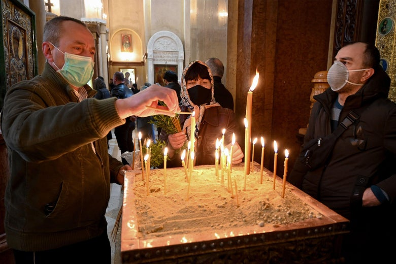 Three people wearing masks light candles in a church.