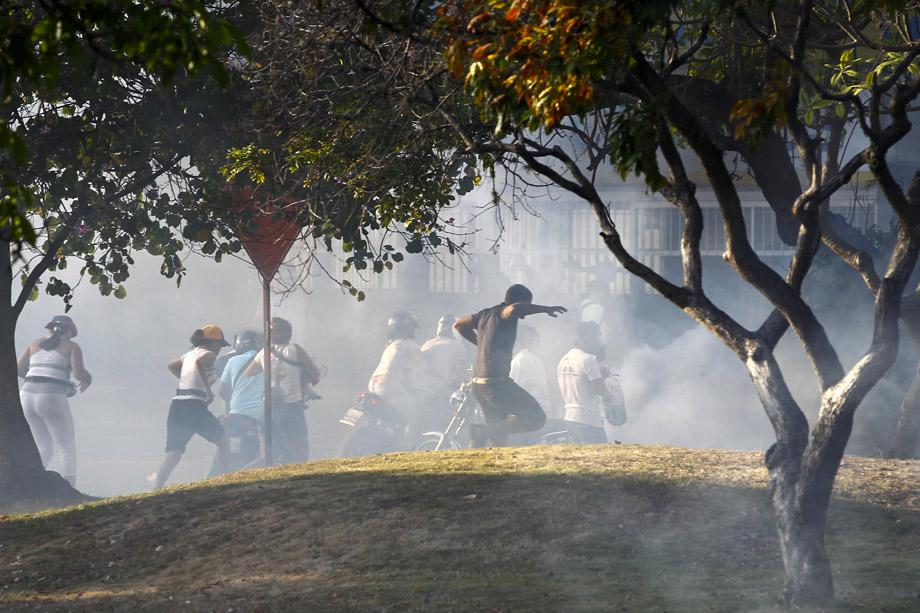 Opposition demonstrators run away from tear gas during a protest against President Nicolas Maduro's government in Caracas February 16, 2014.