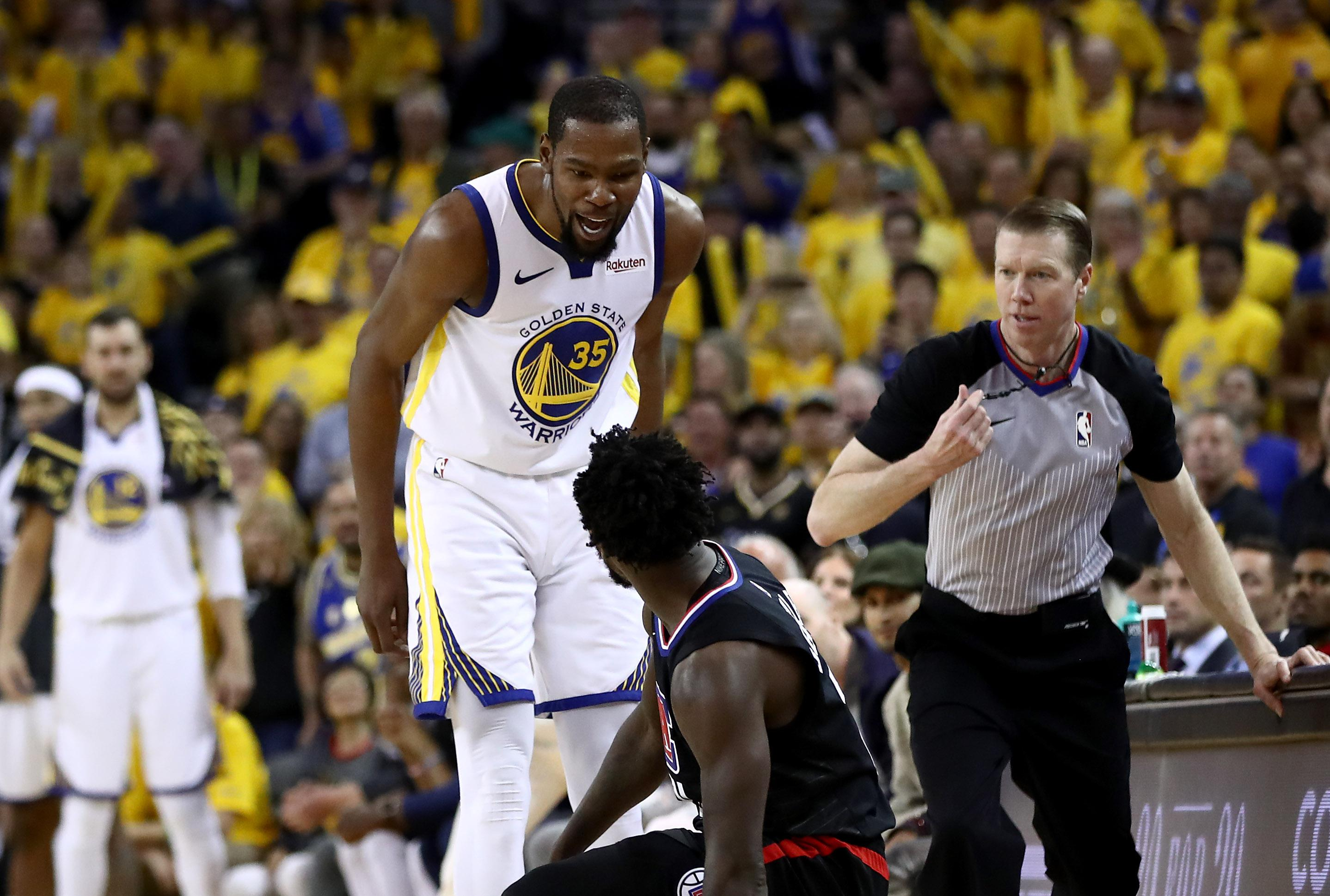 Kevin Durant stands over Patrick Beverley, who has fallen on the court. A ref moves to intervene.