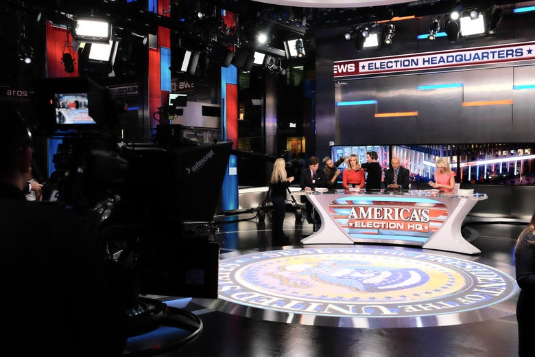 A TV studio set up for election night coverage, with pundits sitting behind a desk