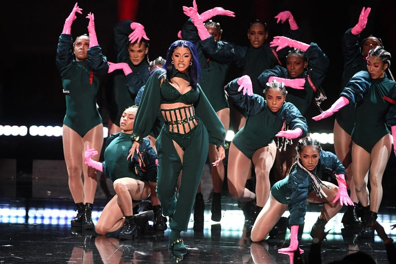 Cardi B onstage, flanked by backup dancers.