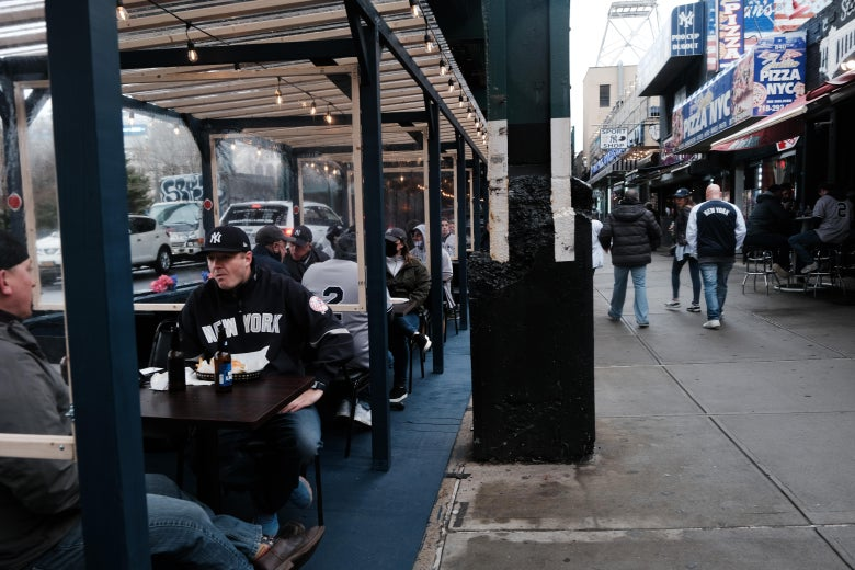People sit at tables in an outdoor dining area