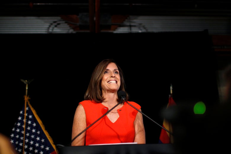 McSally in a red dress at a lectern on a dark stage