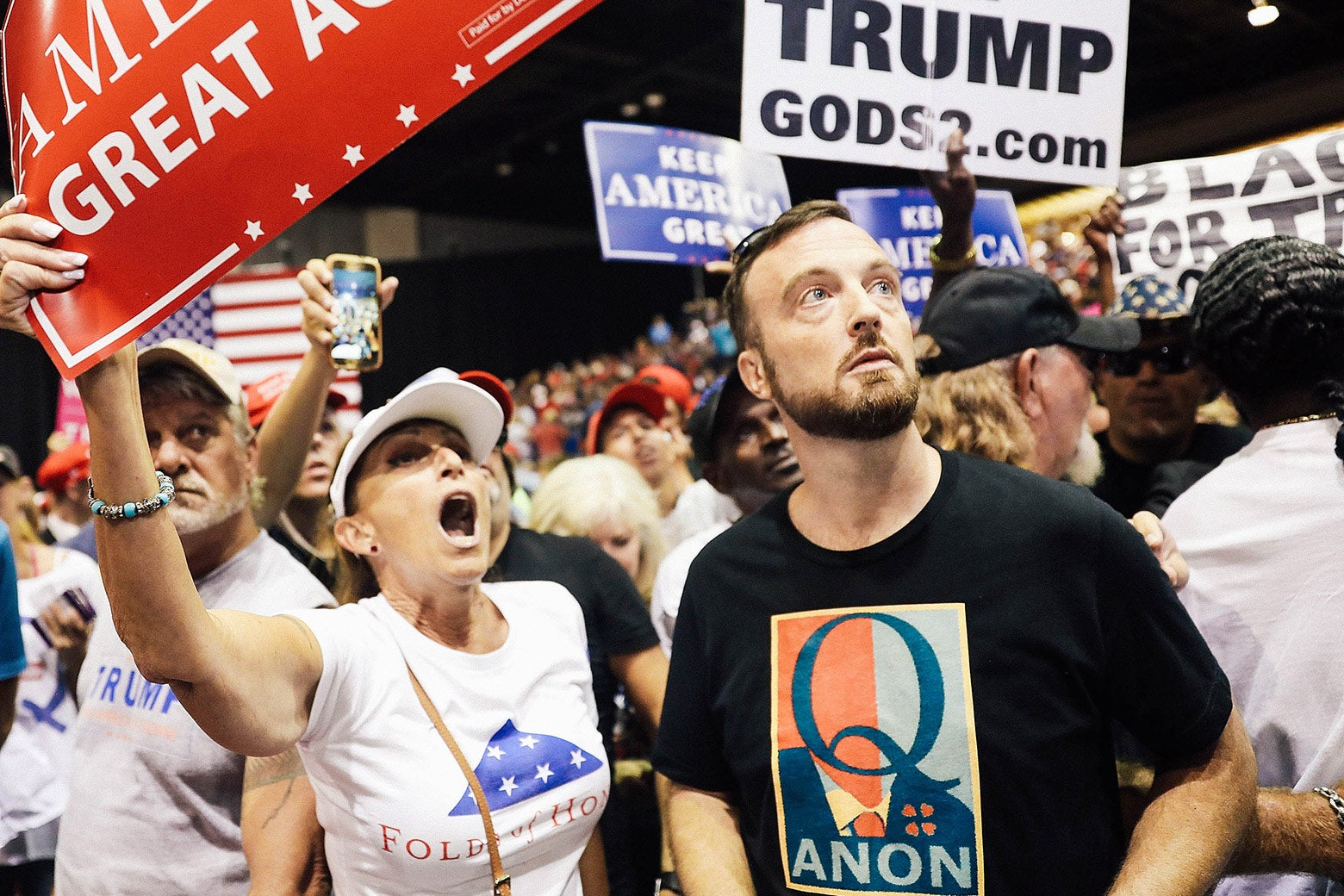 A man wearing a QAnon T-shirt stands amid the crowd at a Trump rally.