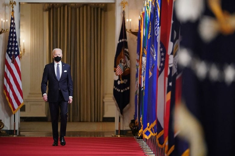 Biden, wearing a suit and a black mask, walks down a red carpet in a hallway lined with flags.