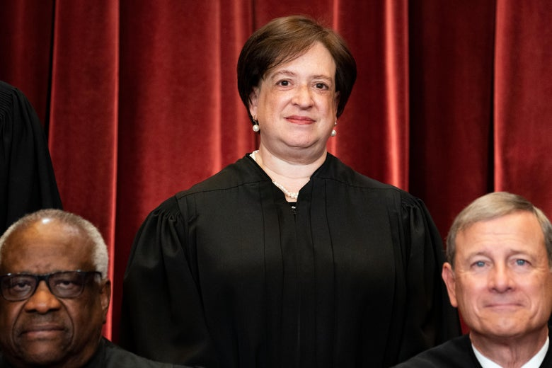 Elena Kagan, Clarence Thomas, and John Roberts in their robes, all posing for the Supreme Court group photo.