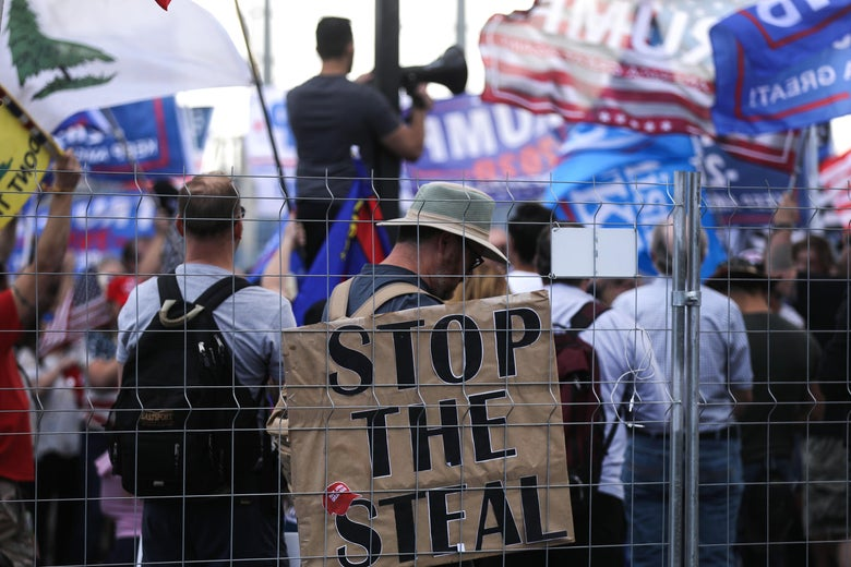 """A crowd stands behind a fence with Trump flags and a sign that says """"Stop the Steal."""""""