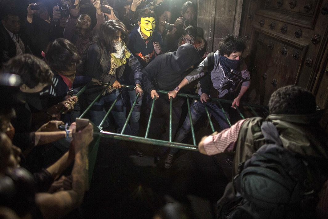 Demonstrators try to knock down the door of Mexico's Government Palace during a demonstration on November 8 in Mexico City.