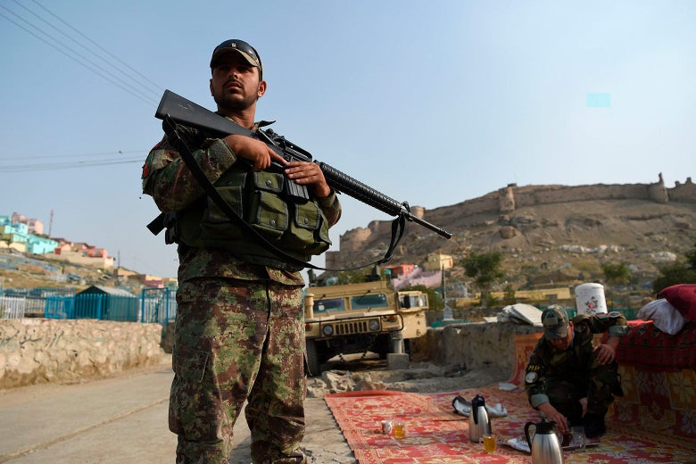 An Afghan soldier stands outside, holding a gun, while another soldier bends down to tend to a tea set on a rug nearby. A military vehicle is in the background.