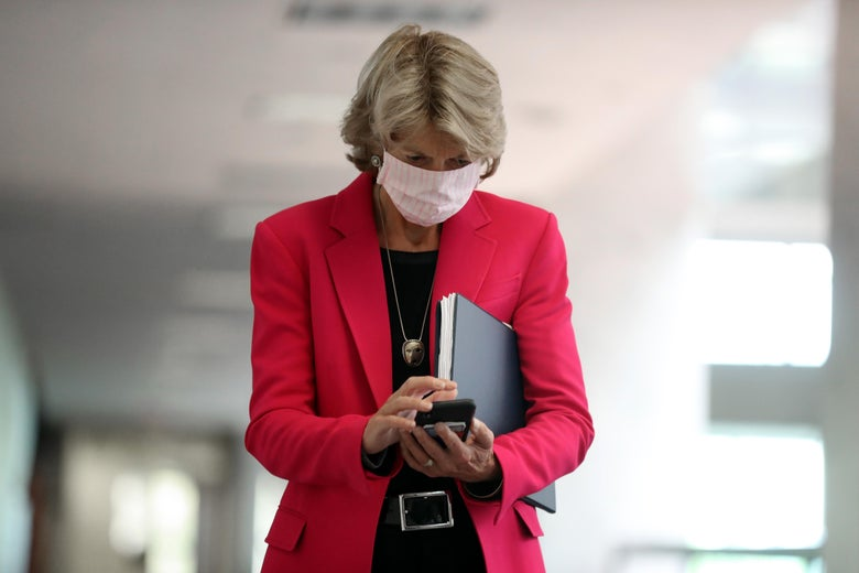 Lisa Murkowski, wearing a pink suit, looks down at her phone.