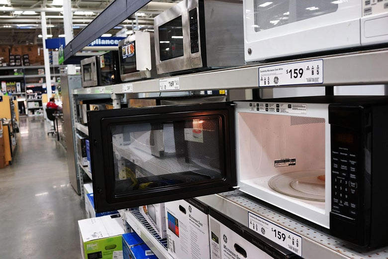 An open microwave oven is seen in a supermarket aisle with other microwaves.
