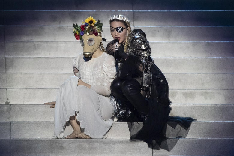 Madonna performs onstage with a dancer wearing a dress, flowers in her hair, and a vintage gas mask.