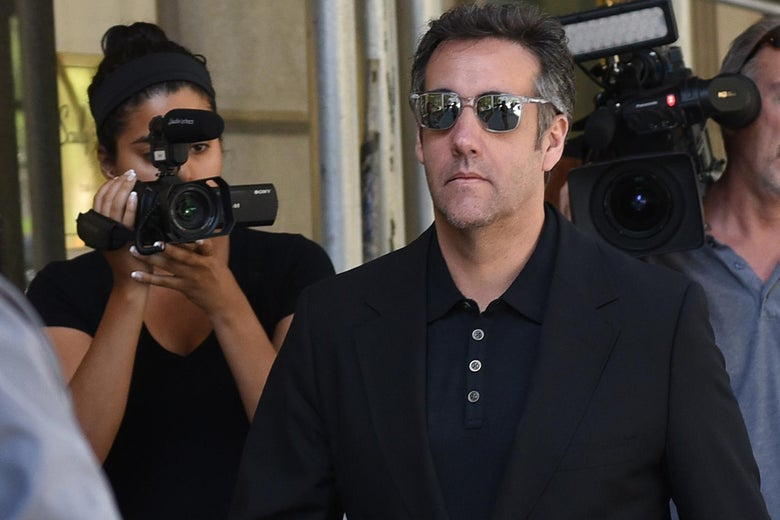 Michael Cohen walks down Park Avenue in New York followed by reporters with cameras.