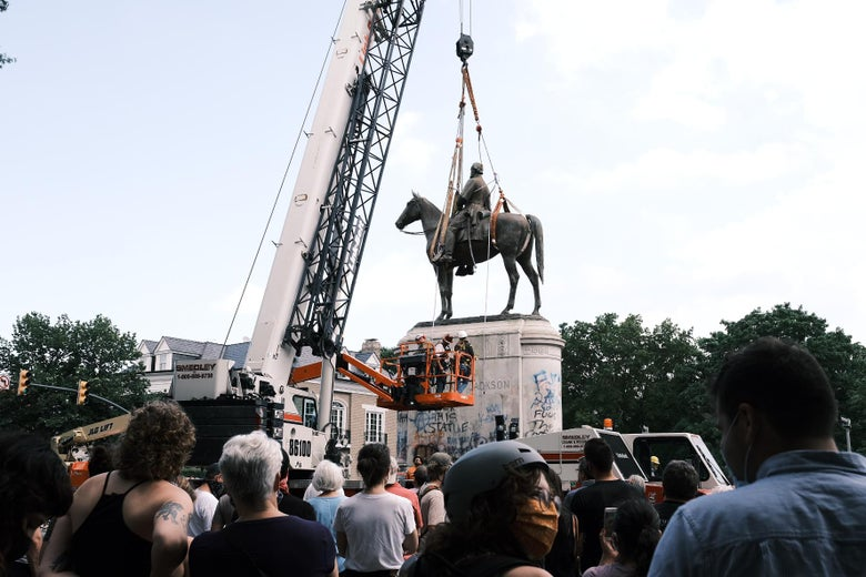 A crowd of onlookers watches as the Stonewall Jackson Monument is removed by a crane.