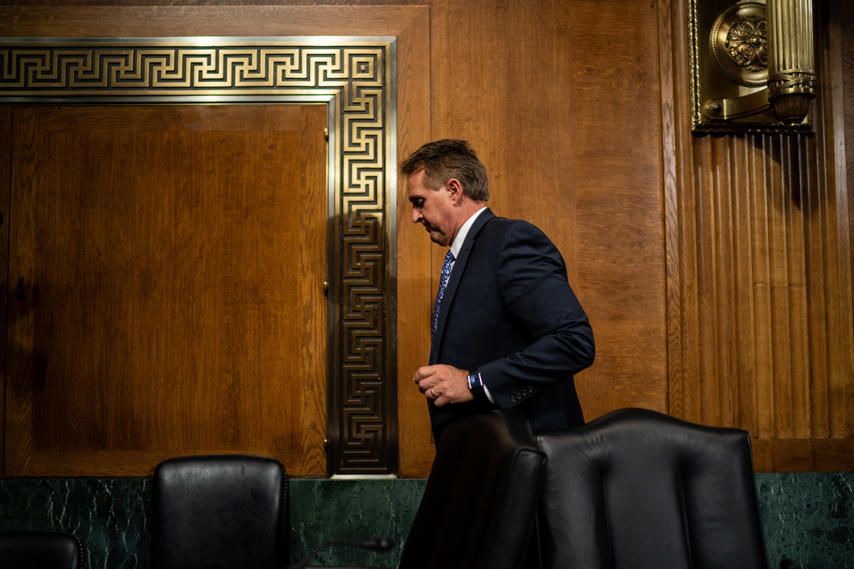 Flake, head down, walking behind chairs in the Kavanaugh hearing room.