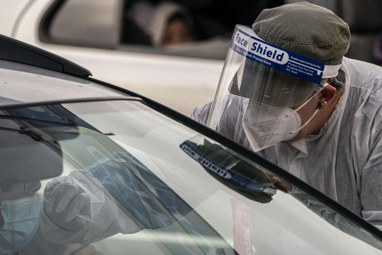 A nurse wearing full PPE administers a Covid-19 test through a car window.