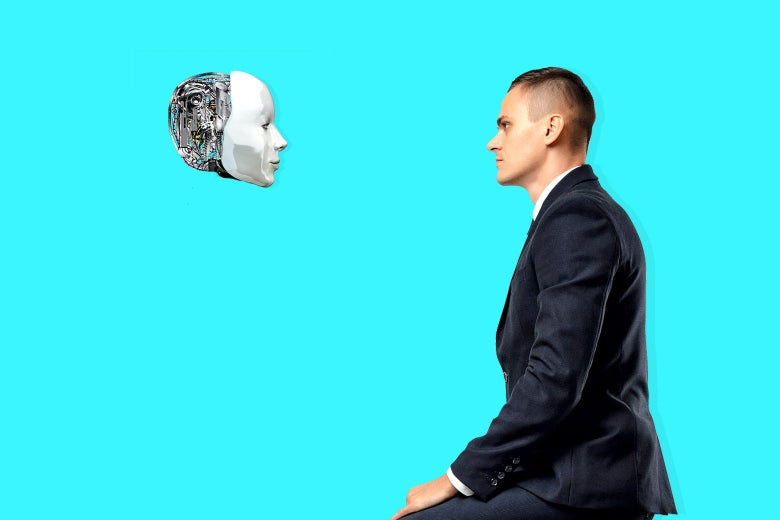 A man in a suit and a robot head stare at each other.