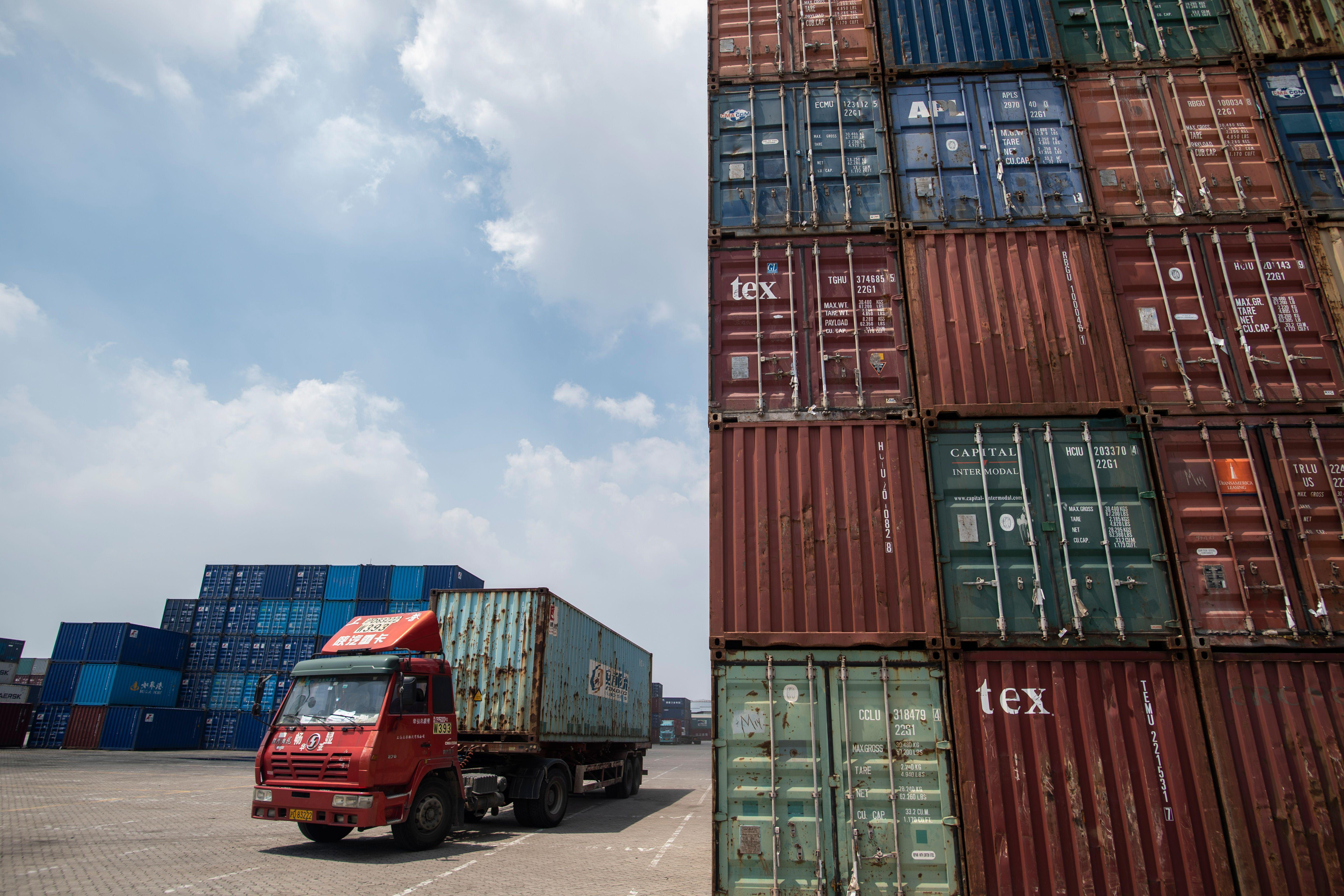 A truck transports a container next to stacked containers at a port in China.