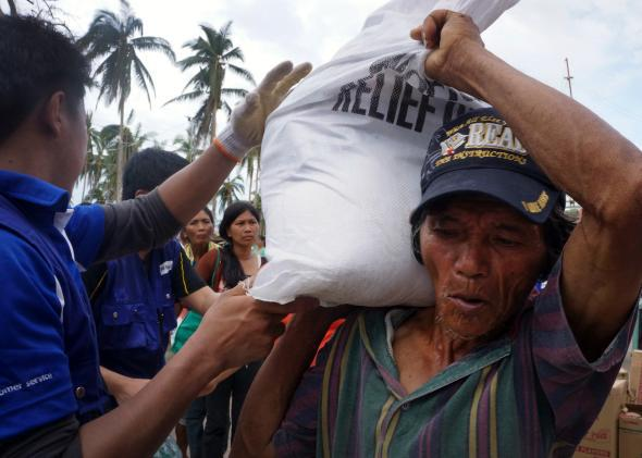 Locals queue for aid from international charity World Vision in an area damaged by Typhoon Haiyan in November 2013.