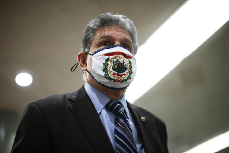 Manchin wearing a mask that has the West Virginia coat of arms on it