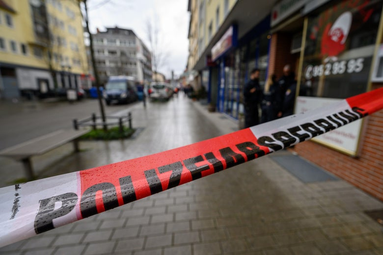 A line of police tape is seen stretched across a sidewalk with storefronts, benches, and trees on it.