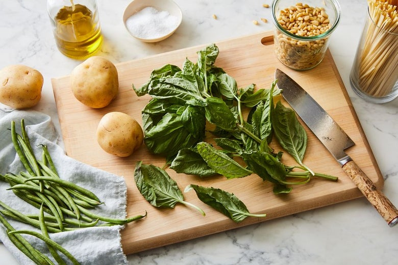 Green beans with potatoes and basil on a cutting board. Containers of olive oil, pine nuts, and raw pasta surround it.