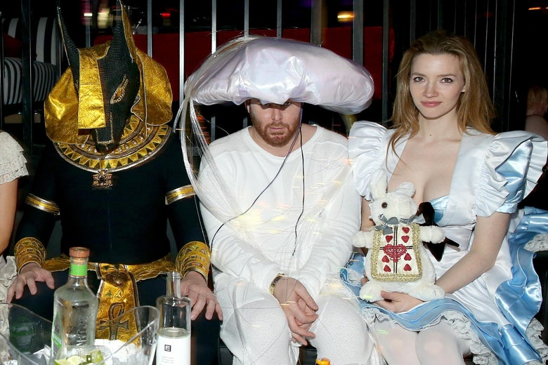 Three people wearing costumes sitting next to each other: one is dressed like an ancient Egyptian deity, one is dressed in all white with a large puffy white hat, and one is dressed like Alice in Wonderland.