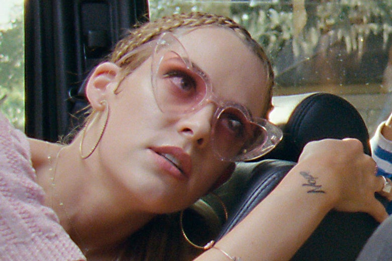 Riley Keough in rose-tinted heart-shaped sunglasses.