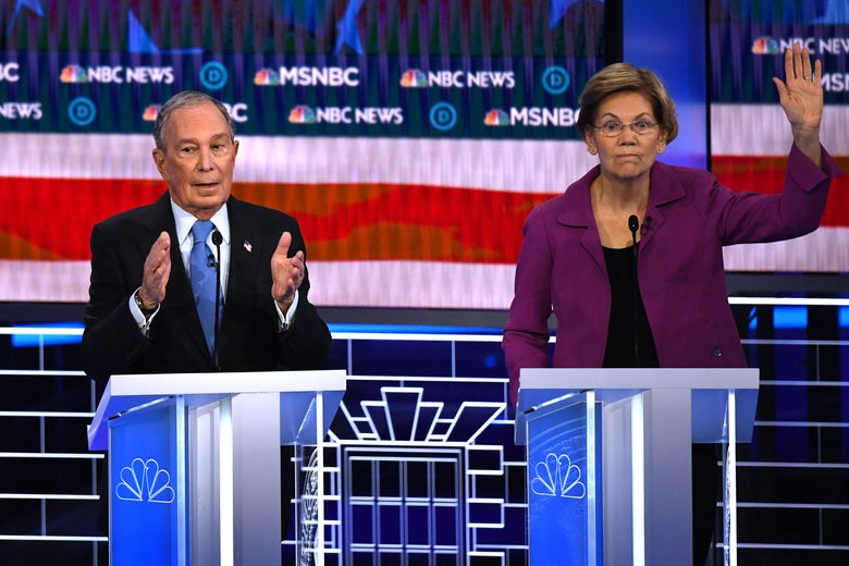 Elizabeth Warren and Michael Bloomberg stand at podiums on the debate stage. Warren raises her hand while Bloomberg gestures as he speaks..