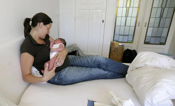 Mother Susan Veenhoff sits in bed with her newborn Maarten Rammeloo, who was born at home in Amsterdam