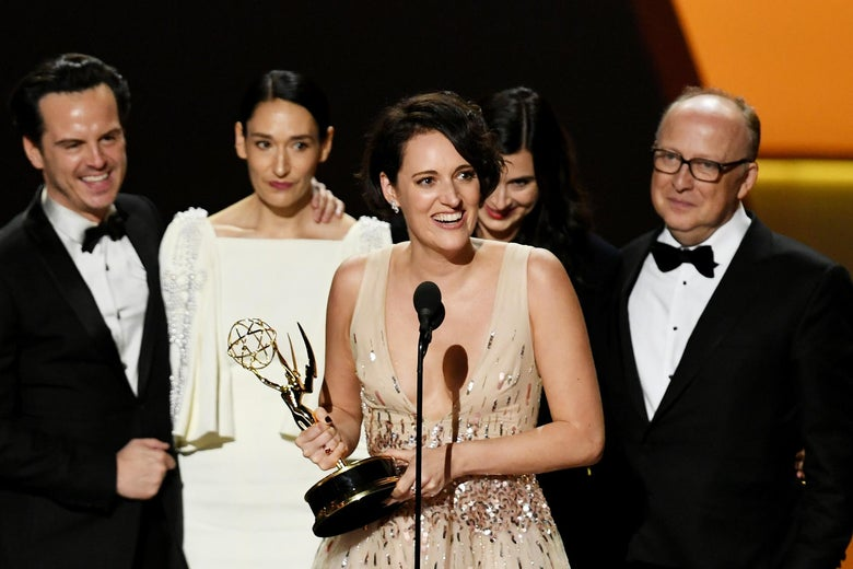 Phoebe Waller-Bridge holds a statuette and speaks into a microphone, surrounded by Fleabag castmates and crew.