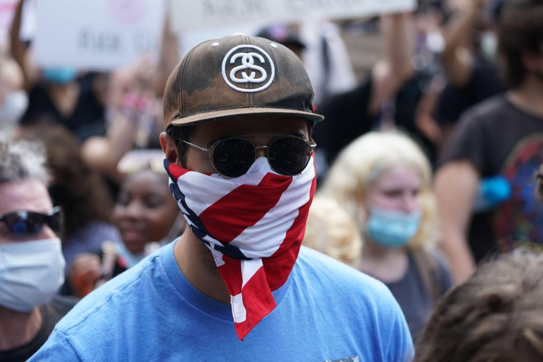 A protester wears a face mask that looks like an American flag.