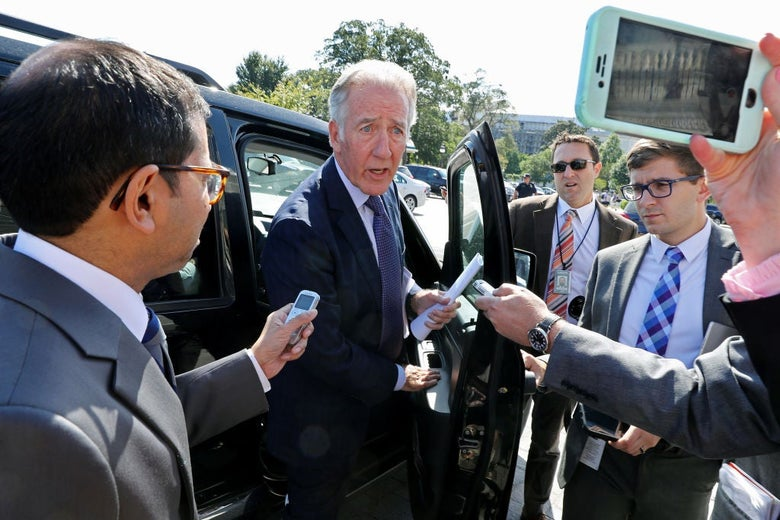 Neal, standing next to the passenger seat of a black SUV, speaks to several reporters.