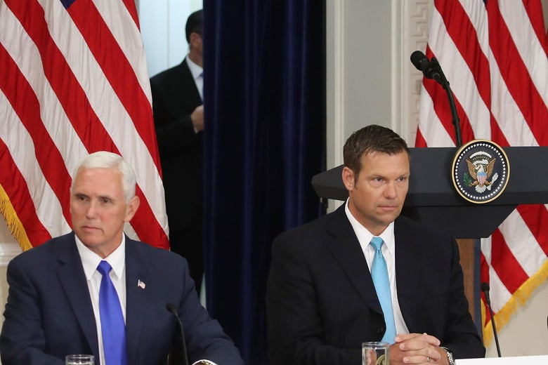 Kris Kobach and Mike Pence seated.