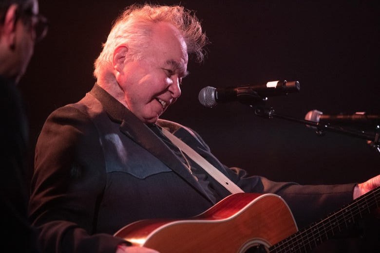 John Prine, smiling, plays an acoustic guitar on stage at the Troubador.