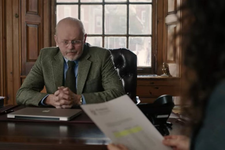 Pembroke's dean sits in a leather chair at a desk.