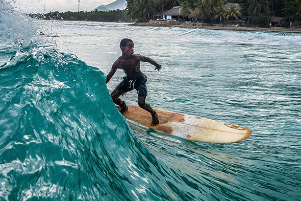 Samson, one of the more experienced surfers in the group, catches a long ride as the wave starts to break, May 5, 2014.