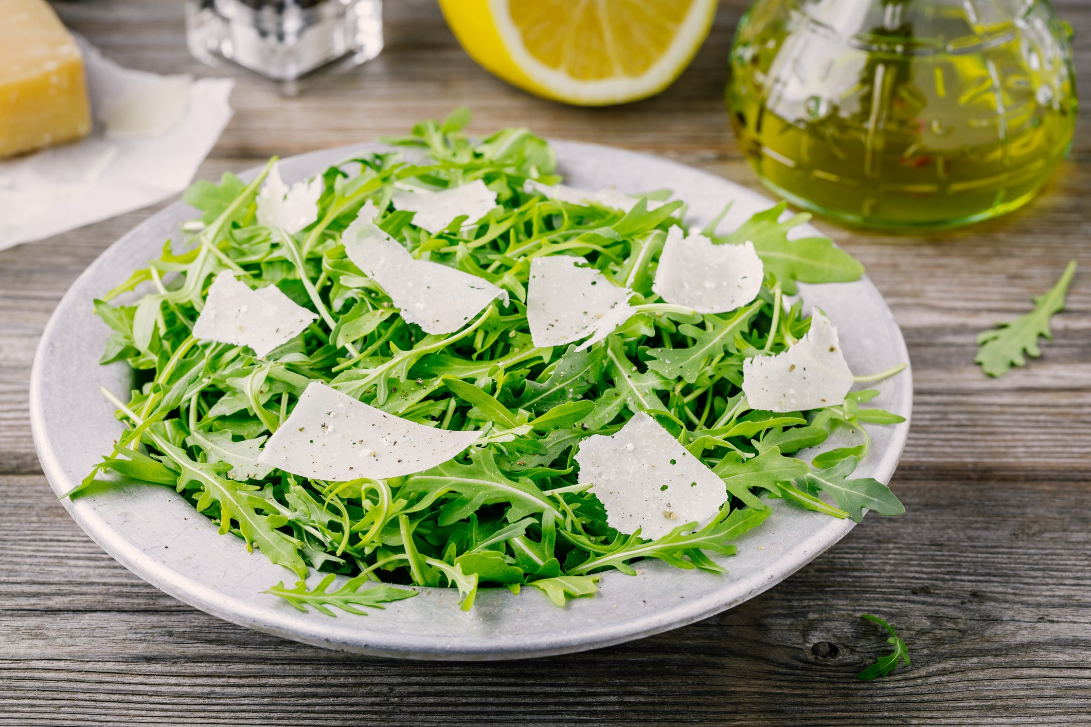 A bowl of arugula with parmesan shavings.