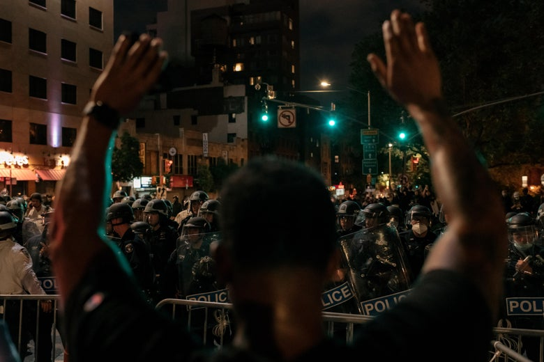 A man protesting police brutality and systemic racism holds up his hands in front of a large contingent of police in riot gear behind barricades confining demonstrators to the Manhattan Bridge for hours during a citywide curfew in New York City at night