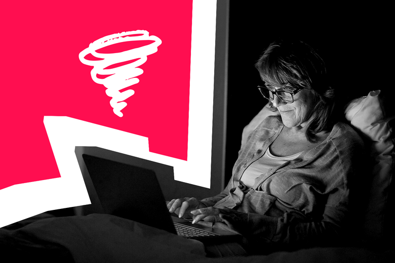 A woman typing on her laptop in a dark bedroom, smirking.