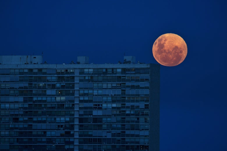 The full moon rises over the Panamericano Building in Montevideo, Uruguay.