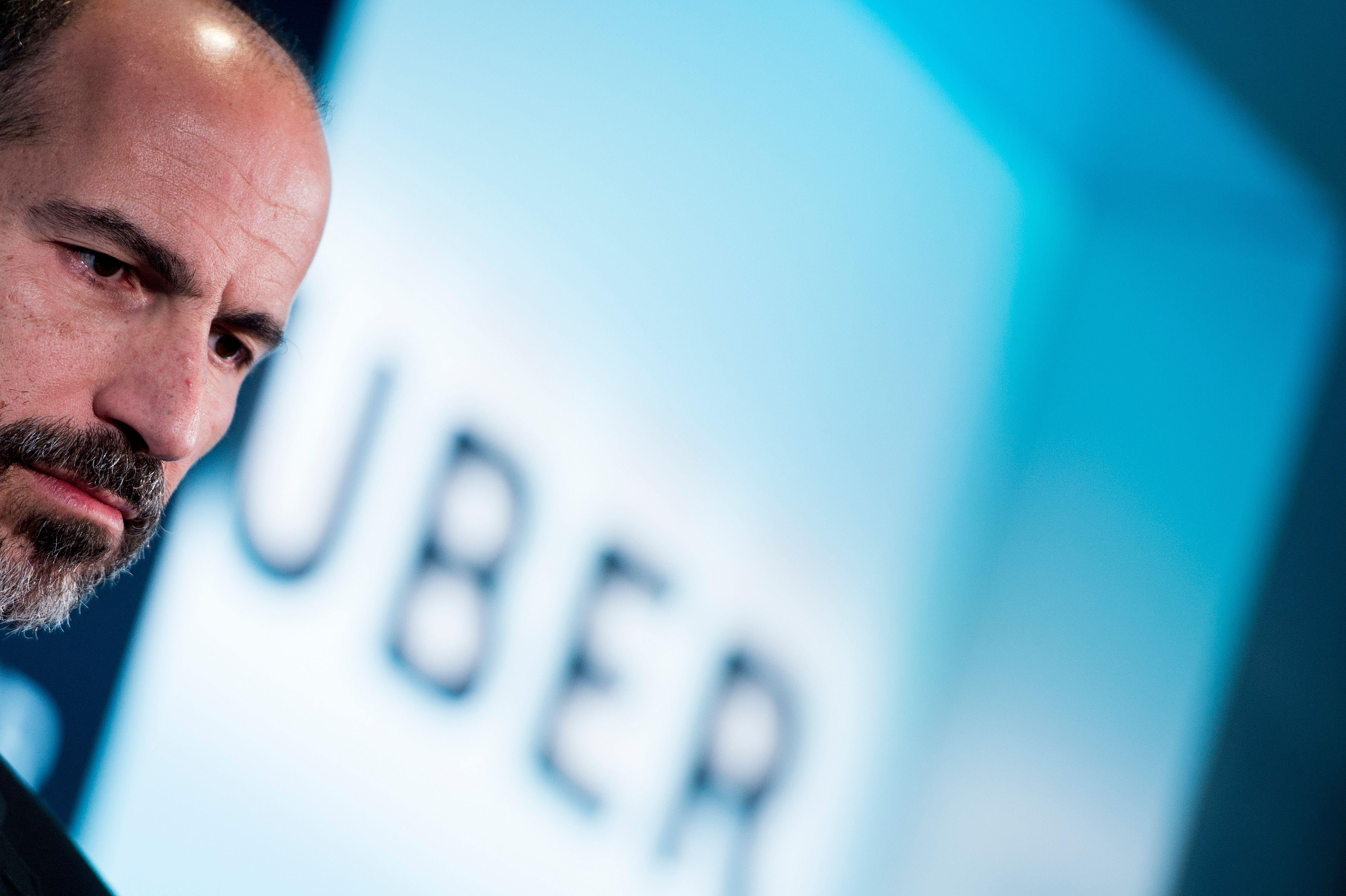 "Dara Khosrowshahi in front of a screen that says ""Uber."""