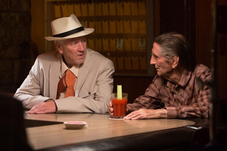 Two men sit at a bar, one in a beige suit and a hat and the other in a button-down shirt.