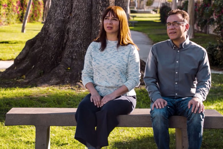 Maya Rudolph and Fred Armisen sit on a bench in a still from Forever.