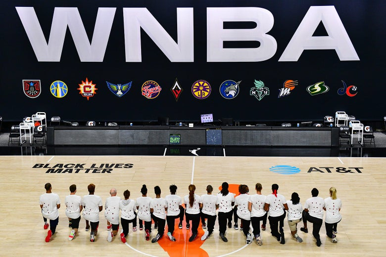 Mystics players wearing protest shirts kneel in a line on a basketball court in front of a big WNBA sign
