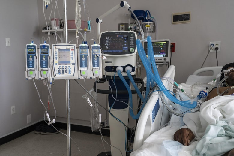 Hospital machinery and a ventilator stand to the left of a hospital bed. On the right, part of a patient's body is visible, connected to the machinery.