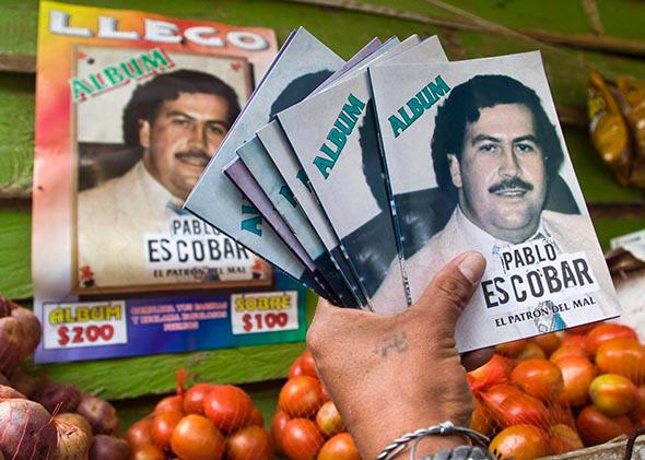A woman shows an album of the late drug lord Pablo Escobar, which is sold in stores in Medellin, August 8, 2012.